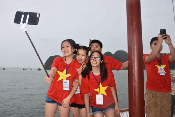 Thời tiết đang mưa nhưng các bạn trẻ kiều bào vẫn rất hí hửng chụp ảnh khi được tham quan Vịnh Hạ Long