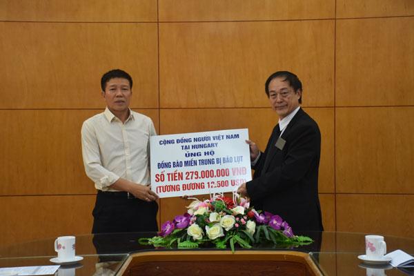 Ông Đinh Văn Đông (bên trái) tiếp nhận tiền ủng hộ của Hiệp hội người Việt Nam tại Hungary